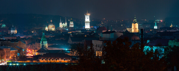 Aerial night panoramic view of churches, city hall and houses roofs in historical old city of Lviv,...