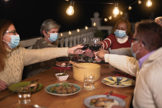 Multiracial senior people celebrate christmas together with dinner outdoor while wearing surgical face mask - Friends cheering with red wine