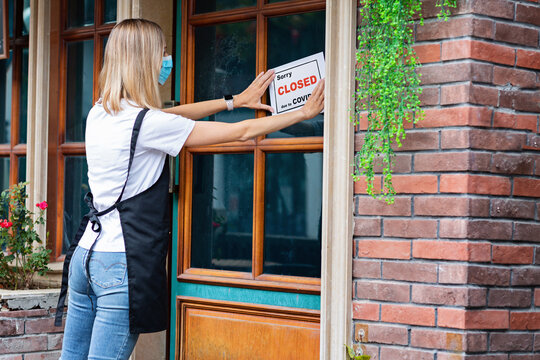 Caucasian waitress woman wearing medical mask puts SORRY WE'RE CLOSED pandemic sign on cafe window. Coronavirus pandemic. Government shutdown of restaurants, shopping stores, non essential services