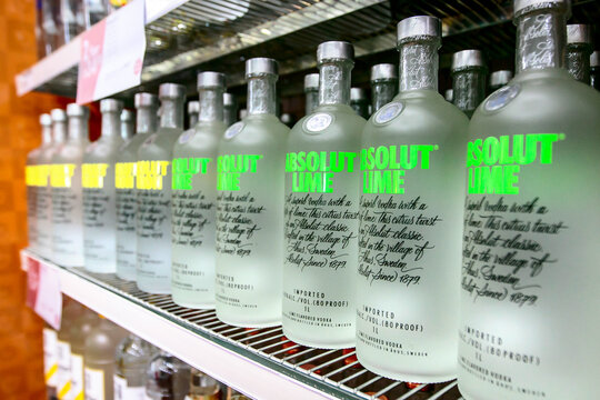 Bottles of Absolut Lime and Absolute Citron vodka stand on a shelf in a liquor store.