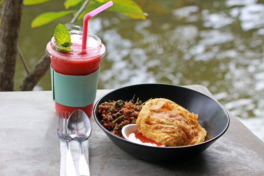 Strawberry smoothie and a traditional Asian meal of omelet with spicy pork outdoors in a garden against a blurred water background