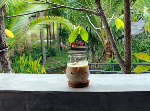 Glass of iced coffee on a concrete breakfast bar with a blurred green tropical garden background