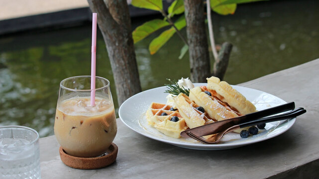 Glass of iced coffee with blueberry waffles outside in a riverside garden setting