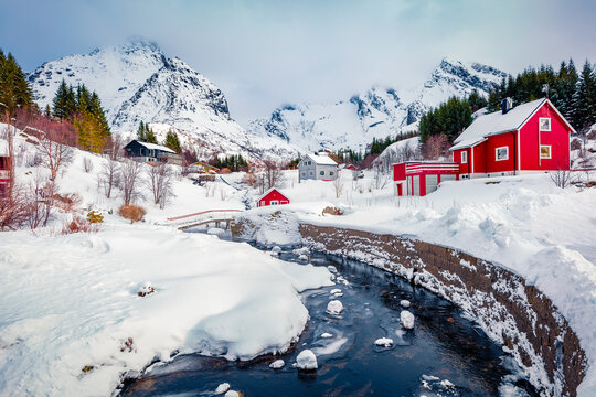 Snowy winter cityscape of Nusfjord town. Fabulous landscape of Norway, Europe. Amazing morning view of Lofoten Islands with red wooden houses and small river. Life over polar circle.