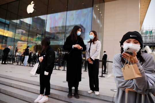 People stand in front an Apple store in a shopping district following an outbreak of the coronavirus disease (COVID-19) in Beijing