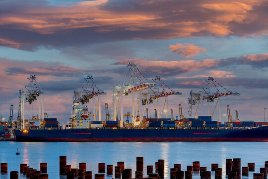 View of container cargo ship and crane bridge in shipyard at sunrise