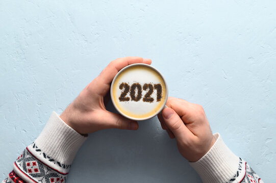 New year background. Male hands hold coffee cup with number 2021 on frothy surface of cappuccino. Pastel blue background. Food creative concept. Top view, copy space