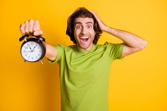 Portrait photo of man keeping alarm touching head deadline late amazed isolated on bright yellow color background