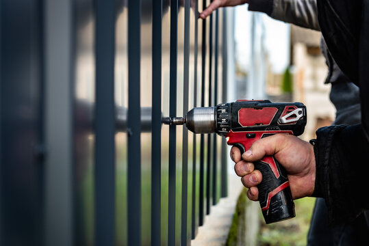 Metal fence installation. The worker is screwing the screw into the metal fence.