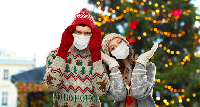 winter holidays, pandemic and health concept - couple in sweaters wearing face protective medical masks for protection from virus disease over christmas tree lights on background