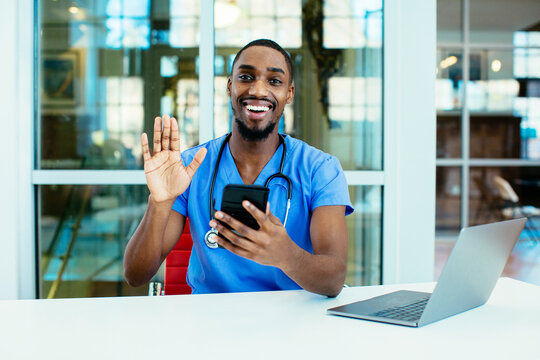 Portrait of a smiling male doctor wearing blue scrubs uniform waving at camera, talk to patient online on phone