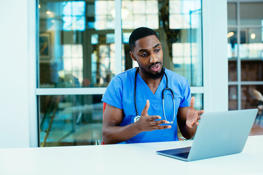 Portrait of a male doctor wearing blue scrubs uniform using laptop to talk to patient online