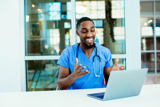 Portrait of a smiling male doctor wearing blue scrubs uniform using laptop to talk to patient online