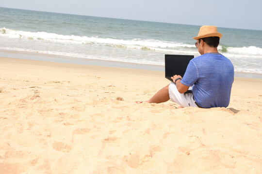 A man using his laptop and working from sea beach, during this pandemic where work from home is part of life , now people can work from anywhere and at the same time have a feel of vacation