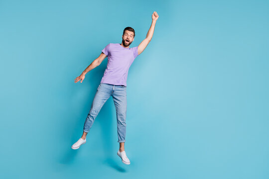Full length body size photo of jumping man pretending superhero flying amazed in casual clothes isolated on bright blue color background