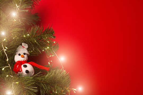 Christmas tree decorated with garland and handmade snowman toy on red background