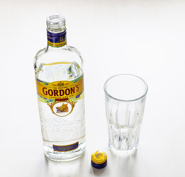 MOSCOW, RUSSIA - NOVEMBER 4, 2020: above view of open bottle of Gordon's London Dry Gin and empty glass on light brown board. Gordon's is brand of London dry gin first produced in 1769.
