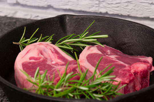 Lamb loin chops with rosemary in a cast iron frying pan.  On a black granite and grey brick background