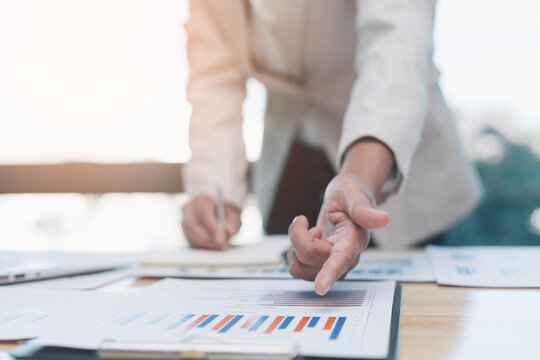 Business women are analyzing and evaluating marketing for a company using graphs on their desks in the office Concept of business risk analysis and assessment