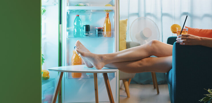 Woman cooling herself in front of the open fridge