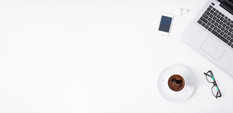 Computer, coffee, smartphone, keyboard on a white background. Concept of an office worker's workspace. Top view with free space.