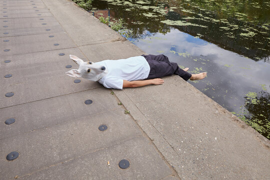 A man wearing a dog mask lies on a canal tow path