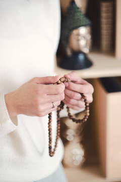 Womans hands with rosary beads at home, closeup