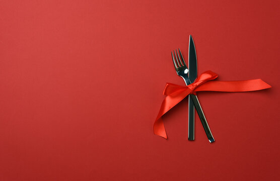 metal fork and knife tied with a red silk ribbon, red background