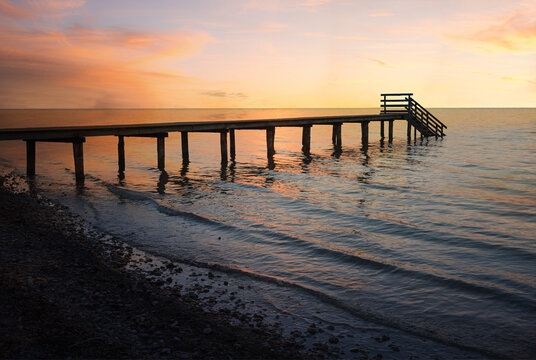 dreamy sunset scenery at stony beach with wooden boardwalk and waves