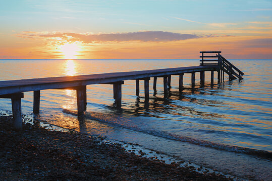 romantic sunset scenery at stony beach with wooden boardwalk and waves