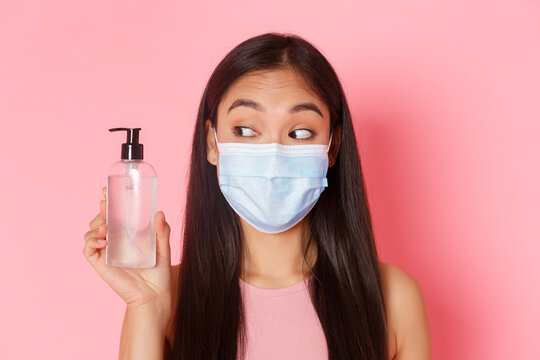 Covid-19 pandemic, coronavirus and social distancing concept. Close-up of cute and silly, pretty asian girl in medical mask looking at hand sanitizer, advice using antiseptics, pink background