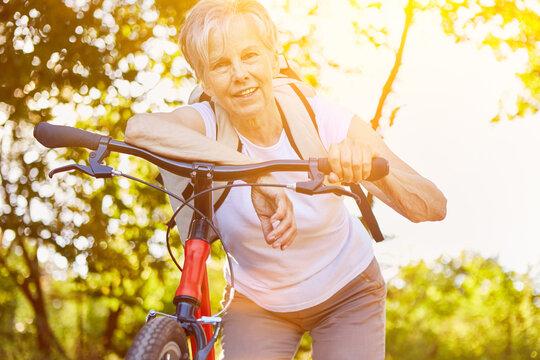 Aktive Seniorin mit Fahrrad in der Natur im Sommer