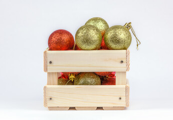 Wooden box with Christmas-tree red and gold balls. Decorations for the holiday