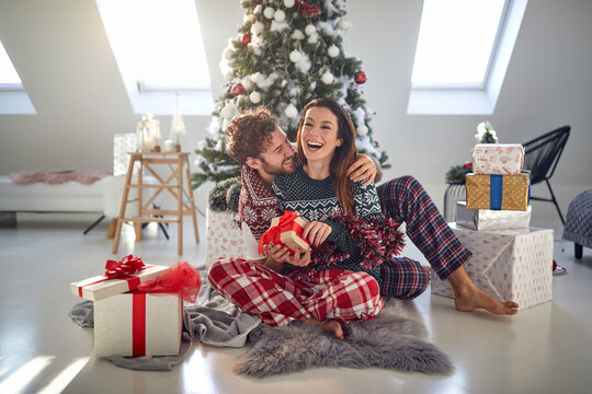 man  hugging gorgeous mature young brunette in front of christmas tree beside pile of presents