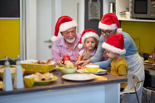 Grandparent and grandchildren love spending time in the kitchen together at Xmas meal preparation. Christmas, family, together