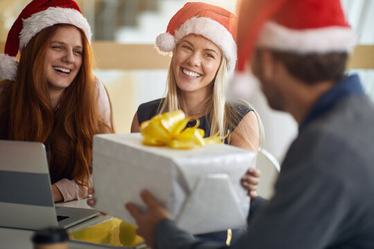 female colleagues receiving gifts at work for christmas