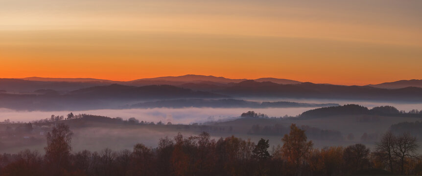 sunset in the mountains - hilly landscape with meadows and forests in a haze, into a yellow and orange-colored sky