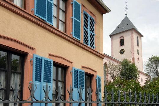 Ville de Sarreguemines, façade colorée, volets bleus et clocher d'une église en arrière plan, département de la Moselle, France