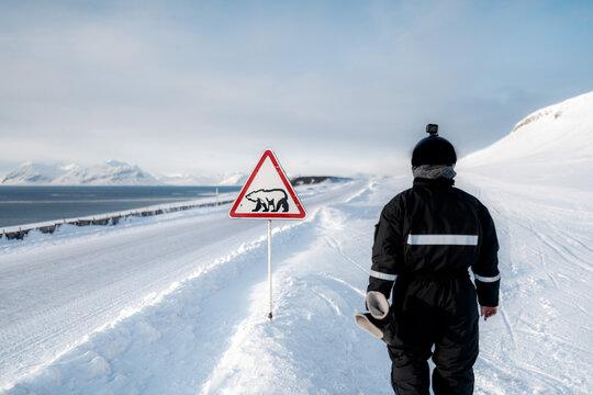 Anonymous traveler near polar bear warning sign