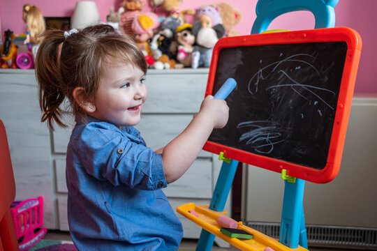 Smiling Three-Year-Old Girl Drawing With Chalk On The Blackboard