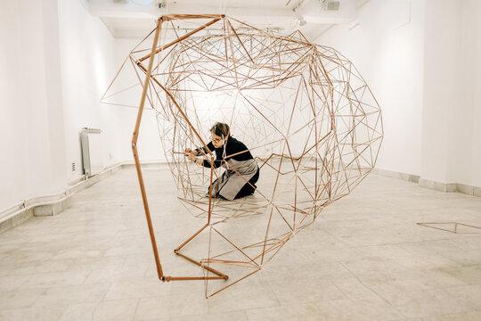 Female Artist Assembling Metal Sculpture In The Art Gallery