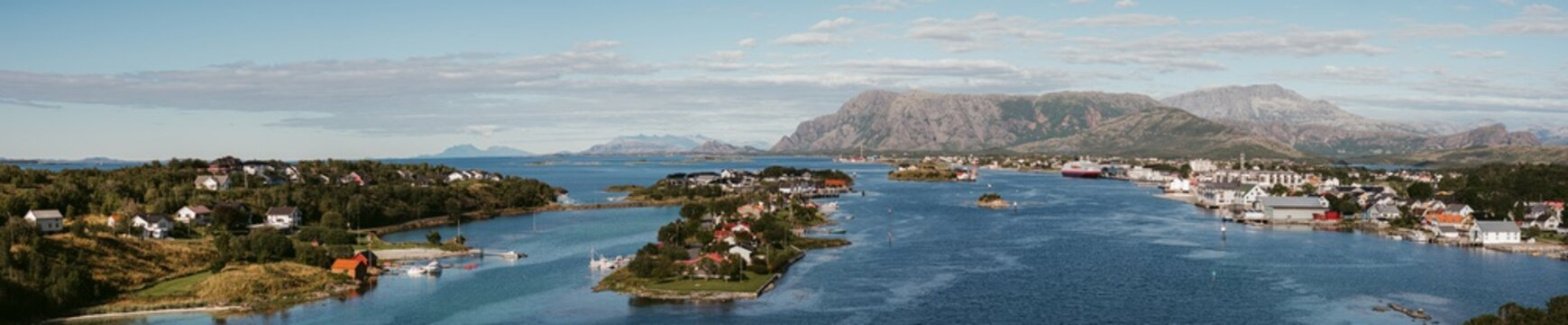 Beautiful panorama of city on islands and along coastline in strait against misty highland at horizon in fair weather