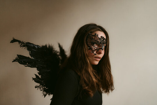 Attractive mysterious woman in black outfit and mask with wings like dark fallen angel
