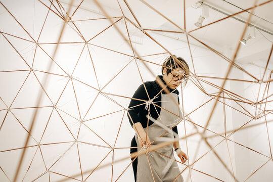 Woman Artist Working On An Abstract Metal Sculpture