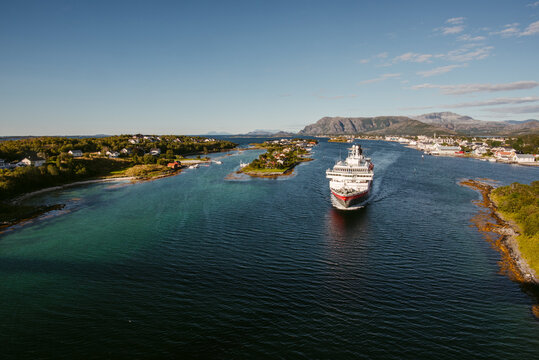 Picturesque scenery with large modern cruise ship in strait against coastal city in sunny day