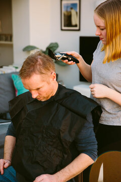 Teenage girl cutting her Dad's hair at home