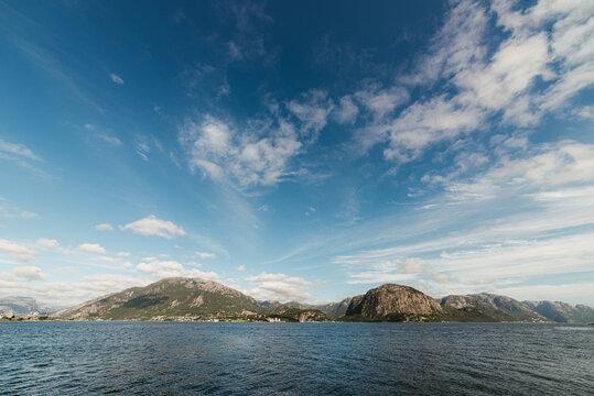 Mountainous seashore against cloudy sky