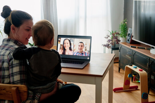 Young mother and toddler having fun with friends via internet