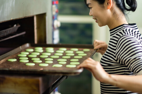 Young woman putting baking tray with macaron into oven