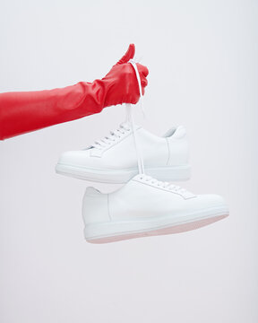 Hand in red leather glove holds white sneakers by the laces.